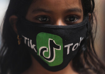 A girl wearing a protective mask depicting the TikTok logo poses for a picture inside a slum in Mumbai