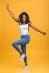 Full length body size photo of inspired african american lady listening music, dancing with eyes closed. Indoor portrait of relaxed black girl isolated on yellow background.