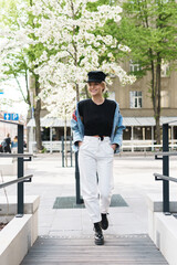 Stylish woman wearing jeans jacket and black cap