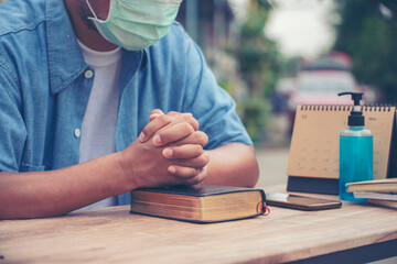 Prayer and bible concept. Asian senior man wear medical mask praying, hope for peace the world and free from coronavirus, Hand in hand together, believes and faith in christian religion at church.