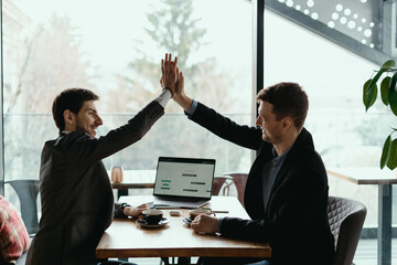 Businessman giving high five to his partner on meeting, positive management team celebrating...