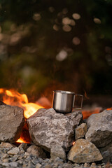 A cup of tea heated on the fire.