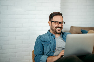Portrait of a smiling handsome man using laptop, copy space.