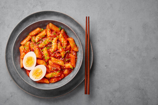Tteokbokki with eggs in gray bowl on concrete table top. Tteok-bokki is a korean cuisine dish with rice cakes. Asian food. Top view. Copy space
