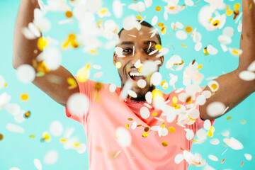 Celebrating, young man with big smile throwing confetti.
