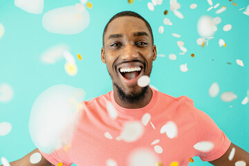 Portrait of a cheerful black man laughing looking at camera with his arms open and confetti falling around