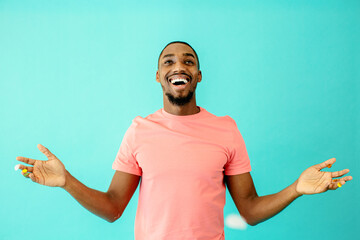 Portrait of a cheerful black man laughing looking up with his hands up to the sides
