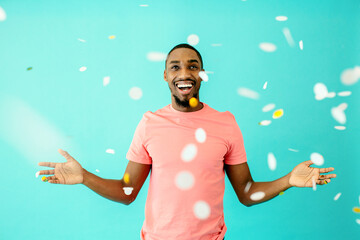 Portrait of a cheerful black man smiling looking up with his hands up to the sides and as confetti falls around.