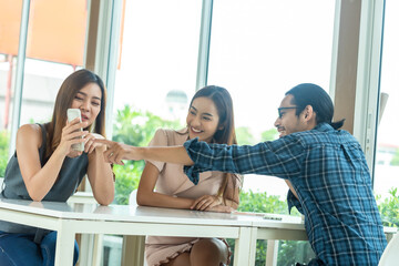 Three friends meet and see each other use smartphone play social media together