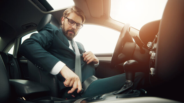 Low angle of businessman sitting in car fastening seatbelt before driving caring about safety