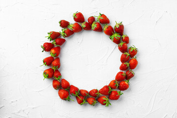 Circle of strawberries on white background, top view