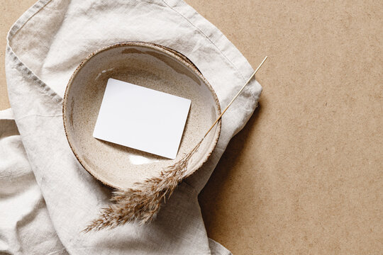 Blank paper sheet card in a bowl. .Minimalist ceramics set over a linen cloth. Business template, copy space, flat lay.