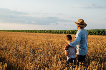 man holding his grandson standing in wheat field