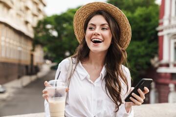 Portrait of young joyful woman using cellphone and drinking milkshake Fotomurales