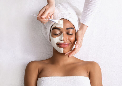Black woman with white mask on half of her face