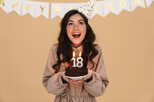 Image of excited young woman smiling while posing with birthday cake