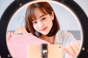 Woman blogging online and streaming live. Asian entrepreneur use social media for business at home. New normal lifestyle and Social Distancing.