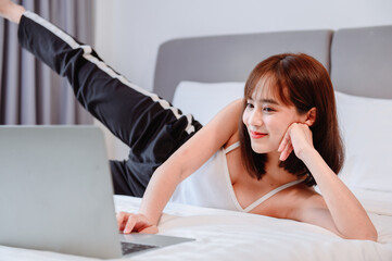 Asian woman workout at home. Online learning for exercise. Social Distancing and New normal lifestyle. Wellness and healthy activity.