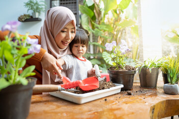 Asian mother helps her daughter take soil with a small shovel from a tray for planting media for potted plants as a home activity
