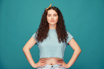 Portrait of confident pretty curly-haired girl in crop top holding hands on hips against blue background