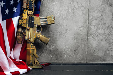 U.S. battle flag and assault rifle near the wall. close up.