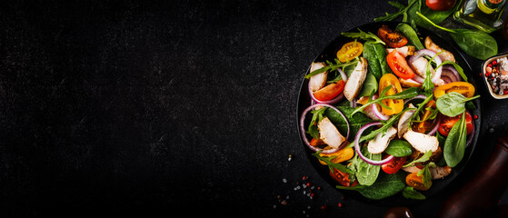 Spring salad with spinach, grilled chicken, cherry tomatoes, arugula, corn salad and red onion. Healthy food concept. Black stone table. Top view. Panoramic banner with place for text