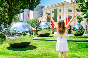 Girl with raised arms among amazing large mirror balls