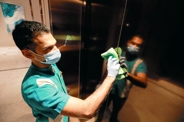 A cleaner wearing a protective mask cleans the elevator doors at the Shangri-La hotel, in Colombo