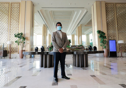 A hotel staff member wearing a protective mask is seen at the entrance of the Shangri-La hotel, in Colombo