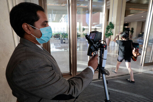 A hotel staff member uses a thermal camera to detect high body temperatures at the main entrance of the Shangri-La hotel, in Colombo