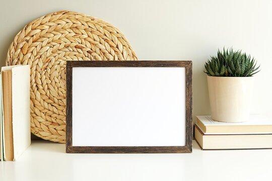 Boho style empty photo frame, dark wood frame mockup, horizontal wooden sign mock-up for artwork, bohemian interior, books, plant on white shelf.