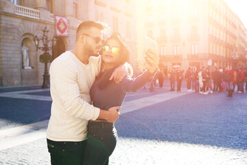 Hipster girl in trendy sun glasses making selfie of herself and her boyfriend by using cellular camera. Kissing couple of tourists taking picture on a smart phone in town square during travel vacation