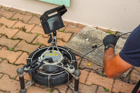 Technicien utilisant une caméra de contrôle pour nettoyage d'une canalisation bouchée