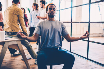 Afro american male member of working team sitting with closed eyes in lotus pose feeling peace...