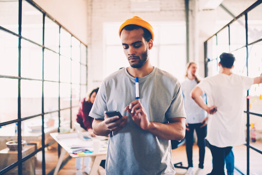 Thoughtful afro american team member reading income message on mobile during work break, dark-skinned student browsing website and checking information while colleagues talking on background