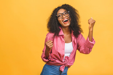 Happy winner! Young African American black woman isolated on yellow background giving a thumbs up gesture.