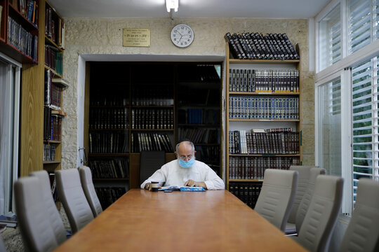 A man studies from a holy book inside a synagogue in the Jewish settlement of Beit El, near Ramallah in the Israeli-occupied West Bank