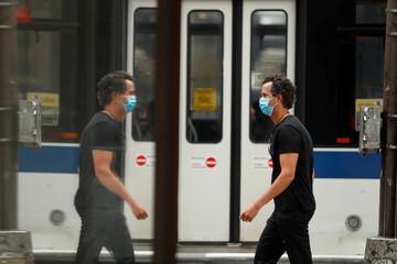 Pedestrians wearing masks walk down the sidewalk  in the Manhattan borough of New York City