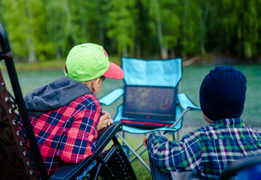 two children are sitting at a laptop