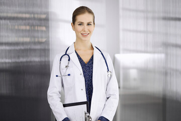 Cheerful female doctor standing in clinic. Portrait of friendly smiling woman physician. Perfect medical service in hospital. Medicine concept