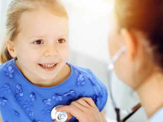Doctor examining a child by stethoscope in sunny clinic. Happy smiling girl patient dressed in blue dress is at usual medical inspection