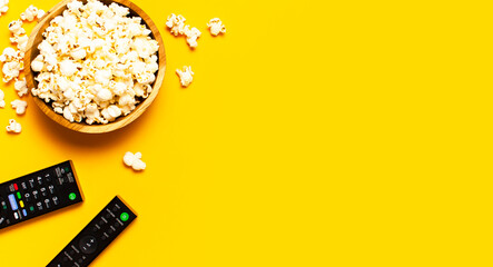 Black TV, audio remote control and popcorn on bright yellow background flat lay top view copy...