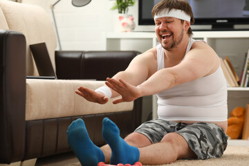 Young attractive fitness man lies on a fat mat with overweight performs stretching exercises and...