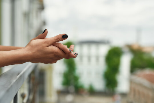 Close up shot hands of woman standing on the balcony and enjoying city view during quarantine