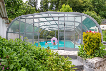 Swimming pool with a roof with kids playi,g inside oin a garden
