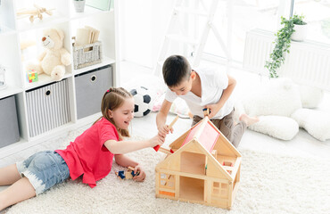 Smiling children playing with doll house