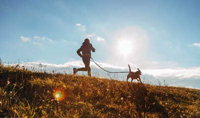 Man runing with his beagle dog at sunny morning. Healthy lifestyle and Canicross exercises jogging concept image.