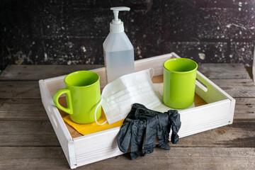 Holztablett mit zwei Tassen zwischen denen Hygieneartikel wie Mundschutz, Einweghandschuhe und Desinfektionsmittel stehen.