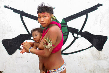 A woman from the indigenous Yanomami ethnic group carries her baby at the 4th Surucucu Special Frontier Platoon of the Brazilian army in the municipality of Alto Alegre