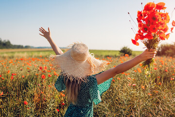 Young woman raised arms holding bouquet of poppies flowers walking in summer field. Happy girl feeling free